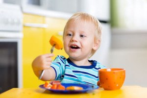 47672341 - cute child little boy eating healthy food in kitchen
